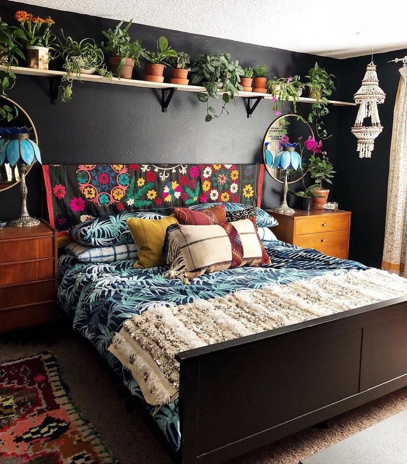 Boho bedroom style with plant patterns on black blankets, combined colorful pillows, carpet patterns, shelves on plant mattresses, brown storage cabinets, white chandelier ornaments
