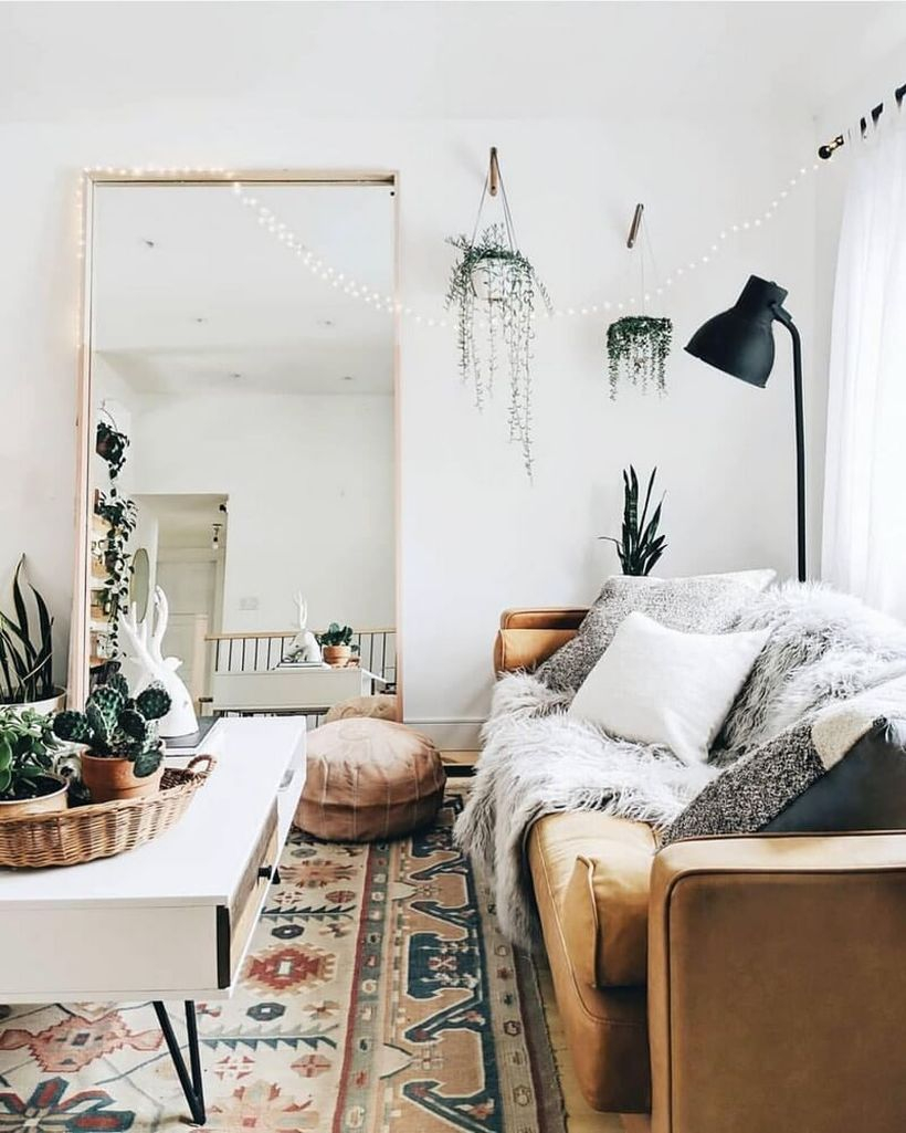 Boho living room design with white patterned carpet, long brown sofa, white and gray sofa cushion, square white coffe table, large mirror and hung green plants