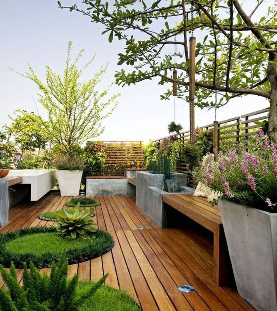 Mesmerizing small rooftop design with wooden seating combined with wooden floor and plants around it to beautify your rooftop garden