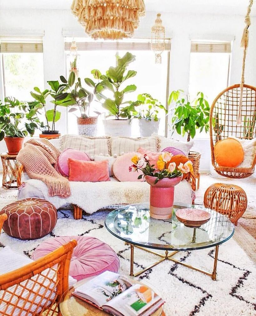 White boho living room design with white sofa, black stripe in white carpet, pink and white sofa cushions, hanging rattan chairs, round glass tables and plants in white fabric pots and rattan pots