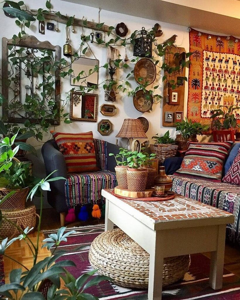 Best boho living room design with blue sofa combined striped fabric, unique patterned sofa cushions, patterned rugs in red hearts, colorful wall art patterned fabric, greenery climbing on the walls and white square tables