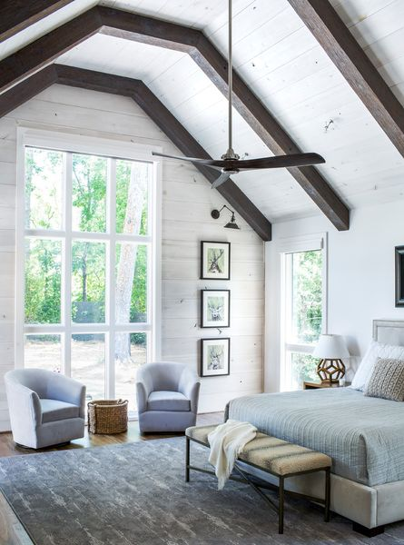 A-large-airy-farmhouse-bedroom-done-with-white-walls-dark-stained-ceiling-beams.-1