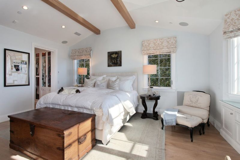 Farmhouse-bedroom-with-light-colored-walls-wooden-beams-floral-curtains.-1