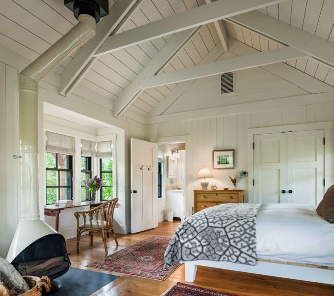 Farmhouse-bedroom-with-window-and-ceiling-beams.-1
