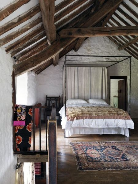 Stone-walls-and-wooden-beams-a-large-metal-bed-and-boho-rugs.-1