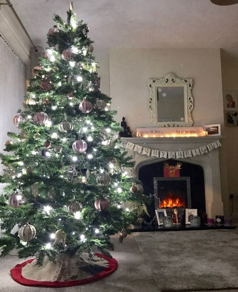 Big green chrismast tree with white light and white ornament